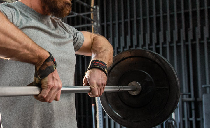 Man lifting barbell using Harbinger padded cotton lifting straps