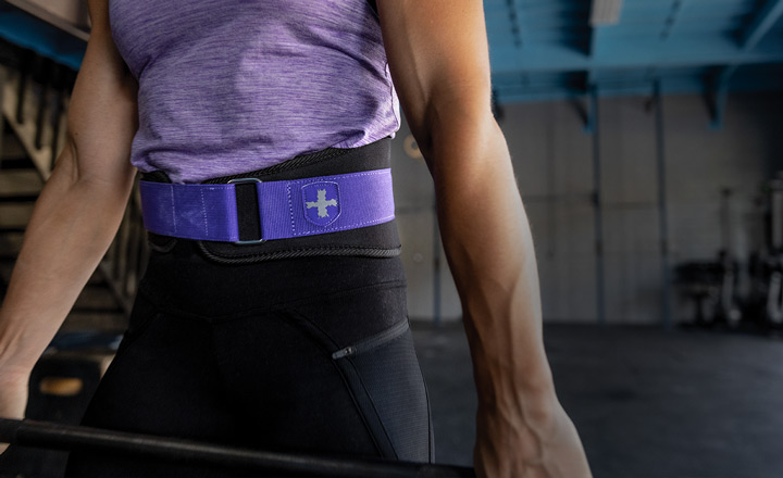 woman lifting barbell using Harbinger purple 5 inch foam core belt