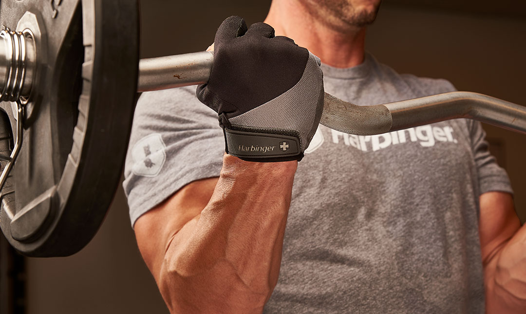 Man lifting a heavy curl bar showing his right hand using the Harbinger Black and grey Bio Flex Elite Glove.