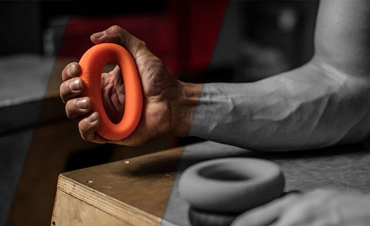 A man squeezing an orange Ergo Grip.